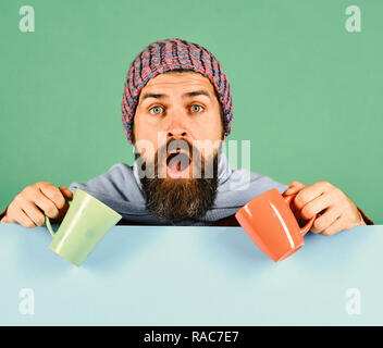 Hipster with beard and shocked face has coffee. Breakfast time idea. Man in warm hat holds orange and green cups on green and cyan background, copy space. Perfect autumn morning and aroma concept - Stock Photo