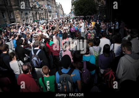 Edinburgh, Scotland - August 14, 2010: Crowd enjoying an outdoor show during the Fringe festival in Edinburgh. - Stock Photo