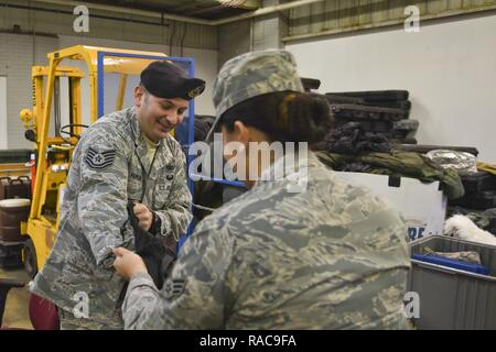 Technical Sergeant Michael Farran, 108th Security Forces, helps an Airmen roll and stuff a sleeping bag during equipment issue at the 108th Wing, Joint Base McGuire-Dix-Lakehurst, N.J., Jan. 17, 2017. The 108th Airmen will support local authorities with crowd control, traffic control, and emergency services. - Stock Photo