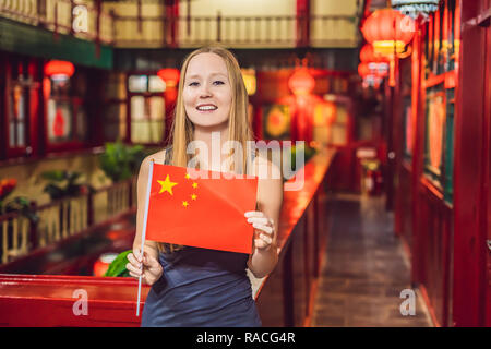 Enjoying vacation in China. Young woman with a Chinese flag on a Chinese background. Travel to China concept. Visa free transit 72 hours, 144 hours in China - Stock Photo