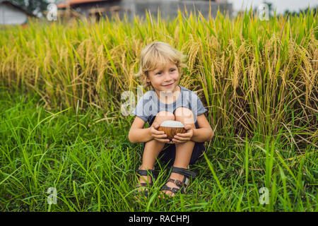 Boy is holding a cup of boiled rice in a wooden cup on the background of a ripe rice field. Food for children concept - Stock Photo