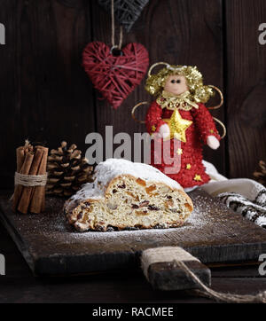 Christmas stollen cake with icing sugar, marzipan and raisins, close up - Stock Photo
