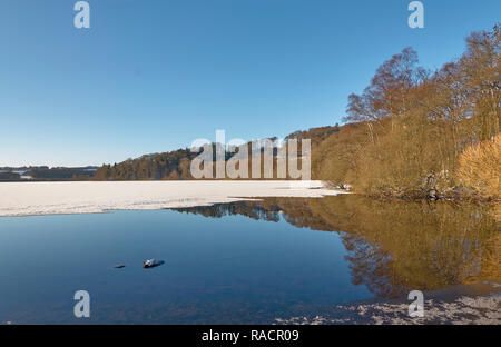 Surface Ice melting at the edges of Loch Clunie in Forneth near Blairgowrie in Perthshire on one Winters evening in January. Scotland. - Stock Photo