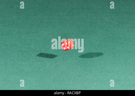 One red dice falling on a green table - Stock Photo