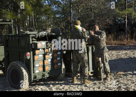 U.S. Marines with Alpha Battery, 1st Battalion, 10th Marine Regiment, 2nd Marine Division (2d MARDIV), prep ammunition for a M120 120 mm mortar system as part of Fire Exercise 1-17 (FIREX) on Camp Lejeune, N.C., Jan. 25, 2017. FIREX 1-17 is a battalion level exercise designed to allow multiple batteries to train together in order to improve internal standard operating procedures. - Stock Photo