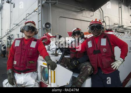 ATLANTIC OCEAN (Jan. 27, 2017) Sailors from crash and salvage division pose for a photo on the flight deck of the amphibious assault ship USS Bataan (LHD 5). Crash stands by in case of fire or emergency. Bataan is underway conducting Composite Training Unit Exercise (COMPTUEX) with the Bataan Amphibious Ready Group in preparation for an upcoming deployment. - Stock Photo