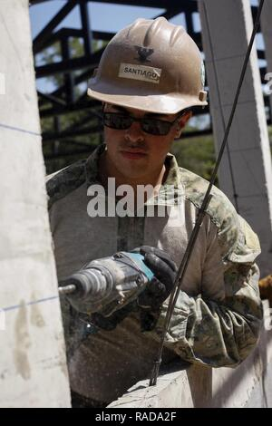 U.S. Navy Equipment Operator 3rd Class Joshua Santiago, with Naval Mobile Construction Batallion 5, drills holes into a window frame at Ban Nong Mi School, Buri Ram province, Thailand, during exercise Cobra Gold, Feb. 1, 2017. Cobra Gold, in its 36th iteration, focuses on humanitarian civic action (HCA), community engagement, and medical activities to support the needs and humanitarian interest of civilian populations around the region. - Stock Photo