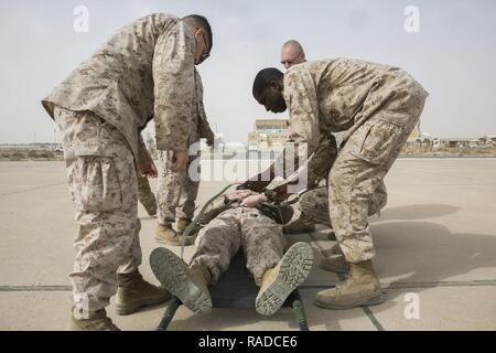 U.S. Navy corpsmen with Special Purpose Marine Air-Ground Task Force-Crisis Response-Central Command strap a simulated casualty to a stretcher during a joint dustoff training event while forward deployed in the Middle East, Jan. 28, 2017. Being able to quickly and efficiently treat wounded personnel on the move with joint forces supports the SPMAGTF's vast crisis response capability. - Stock Photo