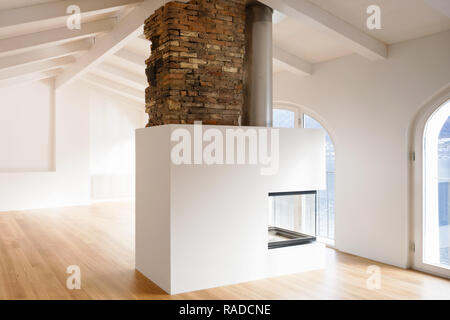 Modern renovated apartment with a large fireplace in the middle of the room which makes the ambieme more comforting - Stock Photo