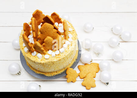 Homemade honey cake decorated with white cream, cookies and marshmallow on white wooden table - Stock Photo