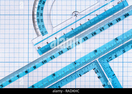 Backgrounds and textures: group of transparent plastic rulers, arranged on graph paper, educational abstract - Stock Photo
