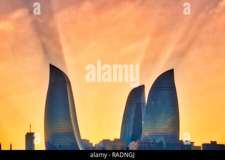 Sun rays behind Flame Towers, Baku, Azerbaijan - Stock Photo