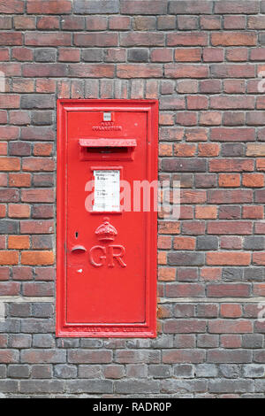 Red post box recessed in a brick wall of Sidney Sussex college, Cambridge university, England. - Stock Photo