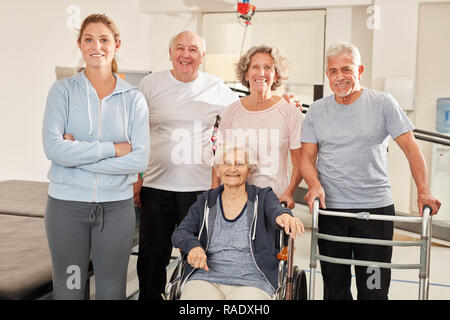 Group seniors in fitness center with trainer is looking forward to the Rehasport course - Stock Photo