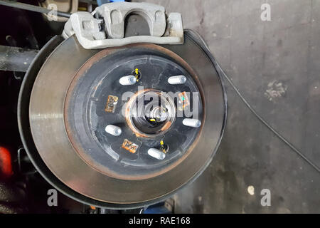 Car brake in the garage, car brake disc without tires - Stock Photo