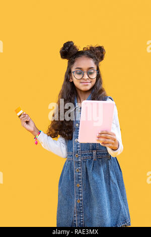 Positive smart young girl doing shopping online - Stock Photo