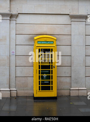 Bath, United Kingdom - October 13 2018:   An old phone box painted yellow and converted to use for First aid and defibrillation in Southgate Street - Stock Photo