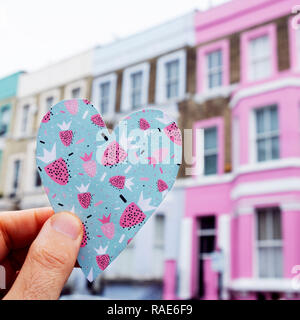 closeup of a caucasian man holding a heart cutout on a colorful paper, in front of a row of colorful houses in the popular portobello road in london,  - Stock Photo