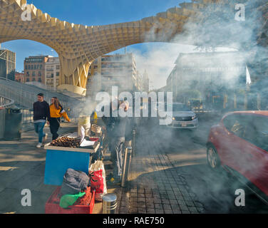 METROPOL PARASOL ENCARNACION SQUARE  SEVILLE SPAIN EARLY MORNING SMOKE FROM ROAST CHESTNUT SELLER AND PASSING TRAFFIC