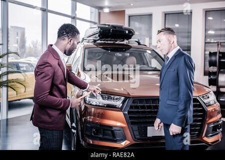 Professional car consultant wearing dark red jacket assisting client - Stock Photo