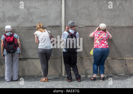 Berlin- Germany – June 2016 :  Visitors look though a  section of Berliner Mauer (Berlin Wall) in Bernauer Strasse. - Stock Photo
