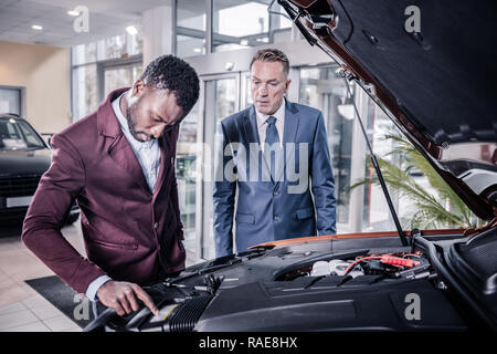 Sales manager of car salon opening front trunk describing car for client - Stock Photo