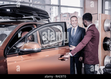 Sales manager wearing dark red jacket opening door of car for his client - Stock Photo