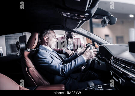 Stylish rich man sitting behind the wheel of his new future car - Stock Photo