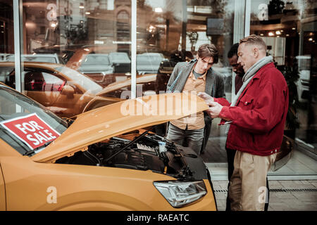 Blonde-haired mature father opening front trunk while choosing car - Stock Photo