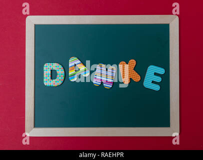 Danke, thank you, Colorful letters shaping the word Danke, thank you in german, on green board with wooden frame, red wall background - Stock Photo