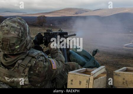 U.S. Army Soldier Spc. Grant Holste, assigned to 3rd Assault Helicopter Battalion, 4th Aviation Regiment, 4th Combat Aviation Brigade, 4th Infantry Division, qualifies with a M2 Browning .50 Cal. machine gun at Novo Selo Training Range, Bulgaria, Dec. 14, 2018. Regionally allocated forces maintain readiness by qualifying on a variety of weapons in realistic environments with allies and partners to ensure interoperability and lethality. - Stock Photo