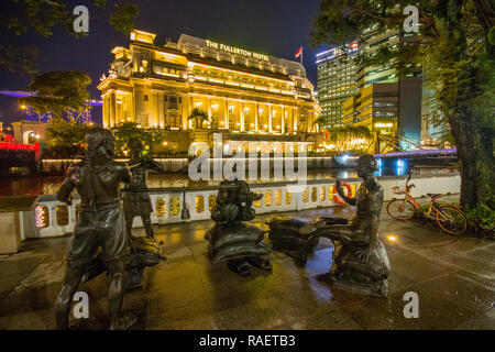 'A Great Emporium', one of the People of the River sculpture series at Singapore River with the Fullerton Hotel in the background, Singapore - Stock Photo