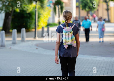 A girl with a colored backpack-bear goes down the street. Rear view. - Stock Photo