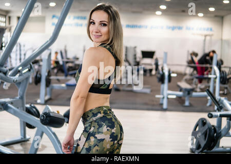 Fitness trainer looks into the camera in the gym - Stock Photo