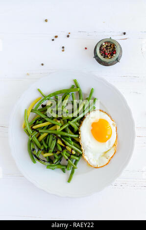 Cooked green beans with sauce balsamico glassa and fried egg in white plate on wooden background. Healthy vegetarian food concept. Top view. - Stock Photo