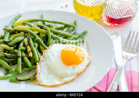 Cooked green beans with sauce balsamico glassa and fried egg in white plate on wooden background with red napkin, knife and fork. Healthy eating. Vege - Stock Photo