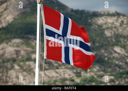 A Norwegian flag floating in the wind, in the background the fjord landscape of the Lysefjord, Norway - Stock Photo