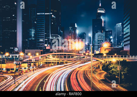 Street traffic in Hong Kong at night. Office skyscraper buildings and busy traffic on highway road with blurred cars light trails. Hong Kong, China - Stock Photo