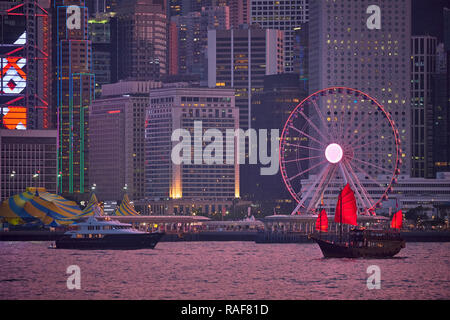 Tourist  junk boat ferry with red sails and Hong Kong skyline cityscape downtown skyscrapers over Victoria Harbour in the evening. Hong Kong, China - Stock Photo