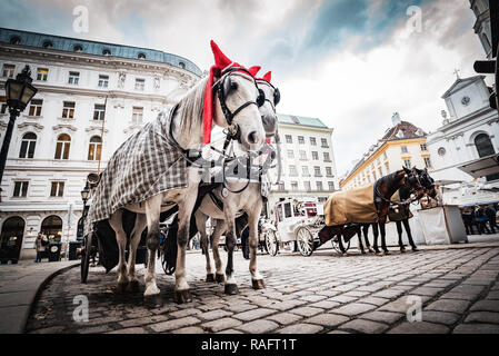 Vienna, Austria - December 10 2018: Horse-drawn carriage on a square downtown next to Hoffburg palace - Stock Photo