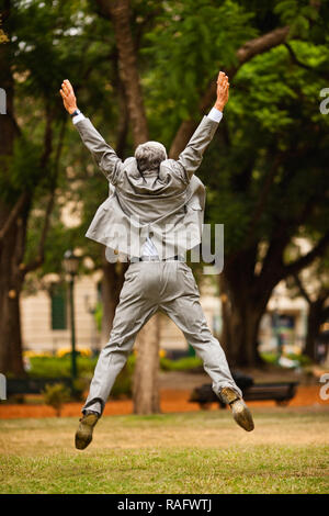Senior businessman jumping for joy in a park. - Stock Photo