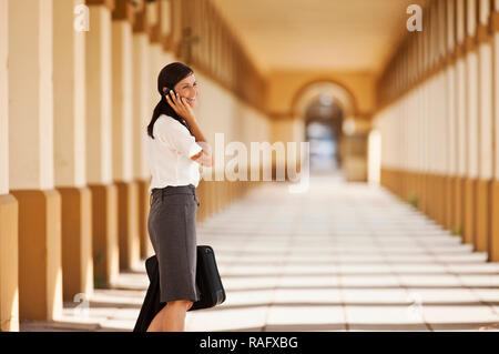 Young businesswoman talking on cell phone in train station. - Stock Photo