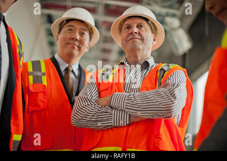 Construction worker and businessman meeting on a building site. - Stock Photo