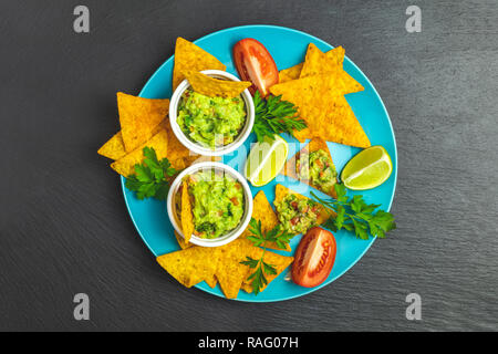 Guacamole and nachos with ingredients in the blue plate on the background of a black stone board. Top view, copy space. - Stock Photo