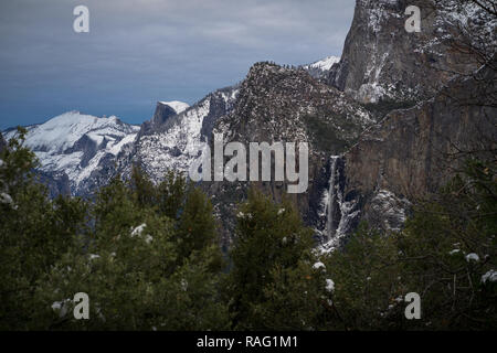 Snowy Yosemite landscape with plummeting Bridalveil Waterfall and Half Dome's granite face. - Stock Photo