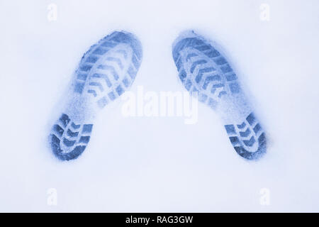 two shoe prints on snow, top view, copy space, cloudy and foggy day, no sunshine, blue light - Stock Photo