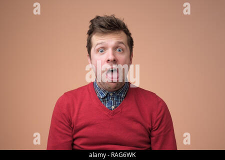Young funny man in white shirt, gesturing shocked or surprised expression with mouth open - Stock Photo