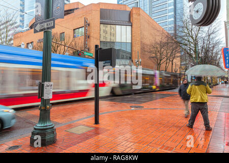 Man stand on the sidewalk with umbrella during the rain, while a light rail train pass by in downtown Portland, Oregon, United States. - Stock Photo