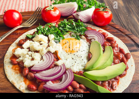 Huevos rancheros breakfast pizza with tomatoes, onion and parsley on rustic wooden background. Selective focus. - Stock Photo