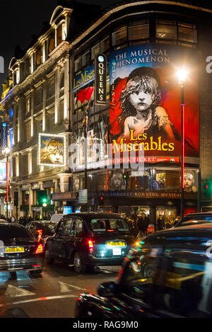 Traffic in London's Shaftesbury Avenue passing the Gielgud Theatre at night - Stock Photo